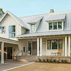 cream exterior with metal roof and reclaimed brick