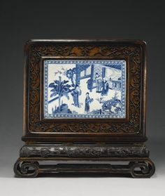 A BLUE AND WHITE PLAQUE MOUNTED AS A TABLE SCREENQING DYNASTY KANGXI PERIOD, THE WOOD FRAME AND STAND 19TH CENTURY. The rectangular panel is well painted on both sides, one with a scene from 'The Romance of the Western Chamber' depicting Zhang Sheng being shown around the monastery by the abbot but distracted by the beautiful Cui Yingying who strolls in the garden; the reverse a riverscape with a scholar crossing an arched bridge; the frame of hongmu wood, 10 in length