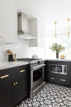 Cle Tile Harold Cement Tiles complement Semihandmade black cabinets adorned with Rejuvenation Lark Bin Pulls & Howard Knobs and finished with a white quartz countertop mounted flanking a Frigidaire stove.