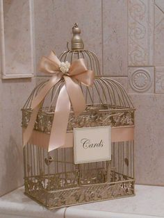 Gold bird cage and ribbons with name cards with calligraphy