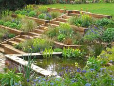 We made a feature of the garden's slope, by designing three terraced levels of planting, with an open flight of steps running through it to the garden's upper section. Description from juliantatlock.com. I searched for this on bing.com/images