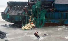 A Chinese fisherman from a stranded fishing boat is saved as South Korean policemen rescue him and other fishermen in Seogwipo on Jeju Island, south of Seoul August 28, 2012. Typhoon Bolaven, with winds of up to 106 mph, buffeted South Korea's west coast, killing five people at sea and leaving 10 missing when two Chinese fishing vessels capsized. (Gang Jae-Nam/Newsis) #