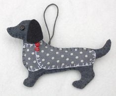 Handmade felt Dachshund ornament for Christmas or any occasion. Clara is a Dachshund made from dark grey felt, with a buttoned jacket in grey and white dotty cotton fabric and a cotton loop for hangin