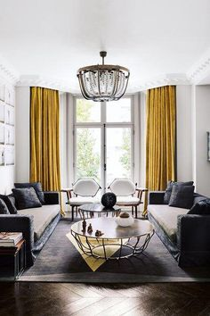 Bright mustard-yellow curtains anchor this grey and white modern living room in a Victorian house designed by Shalini Misra. White walls and herringbone wooden floors provide a clean canvas against which the intricate lines of the pendant lamp and coffee Mustard Living Rooms, Modern White Living Room, Living Room Grey, Modern Room, Small Living, Living Room Wooden Floor, Lamps In Living Room, Living Room Tables, Bright Living Room Decor