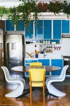 Cozinha integrada com cadeiras descombinadas e prateleira alta com plantas.
