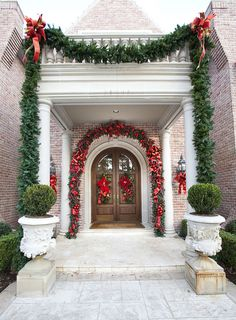 Beautiful Christmas entry way with giant red poinsettias and gorgeous green garland. (thanks for sharing this one ShowMeDecorating.com )