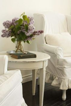 white slipcovered chairs & lilacs