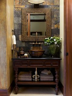 Powder rooms offer a great opportunity to add drama in a small space.  The aged metals, natural stone and wall treatment gives this space rich character.