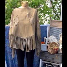 """VTG 70s SUEDE FRINGE GROMMET PONCHO This is such an awesome piece,it's a Vtg 70s tan suede leather fringe poncho,it has grommet diamond patterns, it's shorter in the front & back and longer on the sides, suede is nice and supple not stiff this is a heavy weight poncho, it's missing a 2 1/4"""" area of fringe but can easily be replaced with fringe or use your imagination and cover it up with something like a suede bow etc...it's 26"""" long front & back & 32"""" on sides, neck opening is 12"""" Vintage…"""