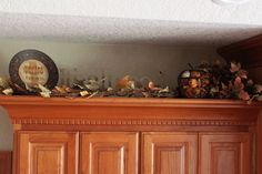ways to decorate above cabinets   Just a little fall on the piano.