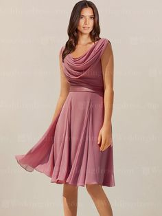 Beach mother of the bride dress features in Chiffon. Bodice is highlighted by the pleated cowl neckline. A slim band sits on the fitted waistline. Zipper back closure is adorned with fabric buttons. Knee length skirt completes the look.