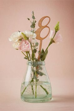 For a pretty spring garden décor scheme, add laser-cut wooden stake table numbers to flower-filled vases.