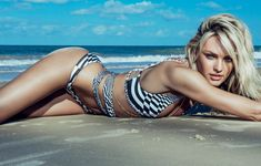 Candice Swanepoel sizzled in a white and navy bondage-style bikini while working the camera on the beach. The 25-year-old blond beauty is a professional when it comes to posing in sexy lingerie and swimwear, so it's no surprise the supermodel nailed the photo shoot for Vogue Brazil's January edition.