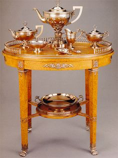 A Faberge complete tea and coffee service set  made in silver and ivory incorporated in  the Karelian style table  made of birch wood with ornate silver trim represents the artistic work and grace of the time.