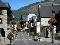 Saint-Lary-Soulan : Spa town and ski resort: street of the village lined with houses, shops and lampposts with flowers ; in the Aure valley - France-Voyage.com