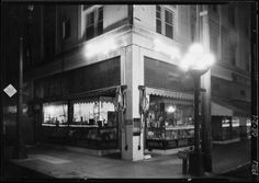 A drug store on the corner of Hope Street and West Pico, shining brightly in a seemingly deserted night-time Los Angeles, 1926.