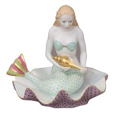Herend's mermaid, with her soft smile, is not sharing her secrets today but even without her song, she still enchants. Perched on a giant clam shell with its pearlized core exposed, she holds a 24K gold tulip shell - maybe a silent invitation to the riches of the watery depths below.