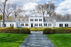 This David Adler mansion has white siding, white trim, black shutters, wood shingle roofing, a central fan window, dual chimneys, and manicured landscaping.