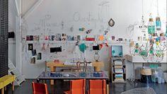 En el atelier de Marie Christophe la mesa azul, las sillas rojas y el banco amarillo son originales creaciones de su marido, el diseñador Emmanuel Fenasse. El colorido conjunto se integra a la perfección con las sillas Diamond, de Harry Bertoia, debajo de cuatro lámparas galponeras.