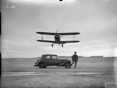 Gloster Gladiator of No. 521 Squadron RAF takes off over a four-door saloon car at Bircham Newton, Norfolk.