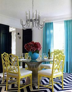 A mid century modern inspired Platner metal and glass dining table is the centerpiece of this designer dining room...that also features bright accents in turquoise and yellow!