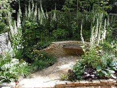 small garden yard bench in dry stone wall and flagstone path with luxuriant vegetation around