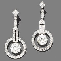 An pair of Art Deco diamond pendent earrings  Of geometric design, each brilliant-cut diamond suspended within an openwork single-cut diamond halo and pierced geometric surmount, to an articulated similarly-cut diamond surmount, principal diamonds approx. 2.80ct. total, remaining diamonds approx. 0.85ct. total, length 3.8cm.