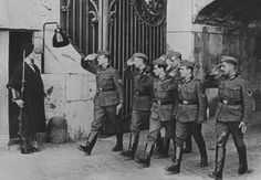 Wehrmacht soldiers salute a Swiss guard at the entrance of Vatican City.