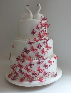 Hochzeitstorte mit Schanenpaar und Schmetterlingsschwarm