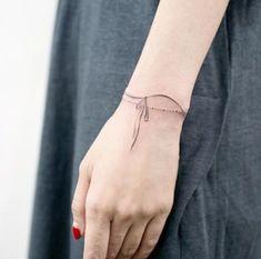 exemple de tatouage femme discret, chapelet de petites perles, fil noir noué, tatouage poignet bracelet