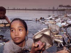 Una niña sacando trozos de plástico de un río contaminado