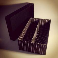Caixa de papelão revestida com tecido e divisória.
