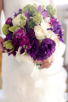 The bridal bouquet will be a clutch of green hydrangeas, dark purple lisianthus, lavender spray roses, purple calla lilies, purple stock flowers, and green bupleurum wrapped in purple ribbon with stems showing