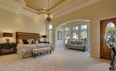 Beautifully decorated tan bedroom with sitting area and high ceiling