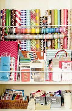 DIY gift wrap organization for the price of a few tension rods! One tension rod high, one low for paper rolls. Another in front of the low one to hold tissue paper, cards, and gift bags. I personally think the ribbon could have been on tension rods too. Like the pictures below……..