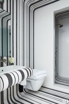 A guest bath in a Manhattan townhouse decorated by Delphine Krakoff is sheathed in Bisazza tile; the sink is by Kohler, and the shower and sink fittings are by Waterworks | archdigest.com