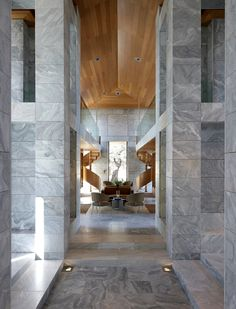 Loving the modern marble walls, wood ceiling and swirling staircase