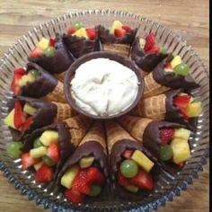 Eine tolle Idee, wie man Obstsalat und Eis servieren kann: Einfach die Eishörnchen in geschmolzene Schokolade dippen, festwerden lassen, mit Obst befüllen und in die Mitte einen Becher Eiscreme oder Sahne stellen.