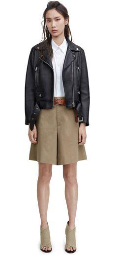 Black leather biker jacket, white shirt, brown belt, beige skirt, beige shoes