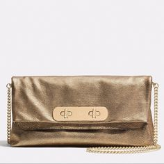 """SALE Coach NWT Swagger Gold Metallic Handbag Gorgeous BRAND NEW with tags 100% guaranteed authentic COACH gold metallic clutch bag. This stunning Swagger clutch from Coach charms us with its versatile and stylish side, perfect for the modern woman. This is a gold double carried bag with removable adjustable shoulder strap. Material: Leather Calfskin. Clutch has flap and revolving buckle closure w/inside zippered pocket. 8 x 33 x 17 cm ( 3.15 X 12.99 X 6.69""""). Shoulder strap : 90 cm. Coach…"""