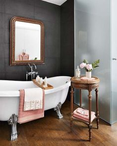 Louis Philippe mirror and the accent table combined with the clawfoot tub and dark wall color brings drama to this bathroom!