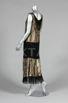 A gold lamé cocktail dress, late 1920s-early 1930s, with tiers of black mesh and gold lamé, draped bib to rear neckline,