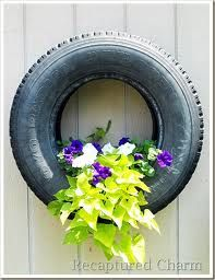 Flower garden in an old tire hanging on an old shed