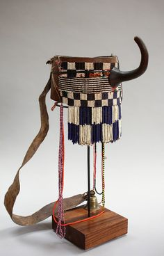 Animal hide, old glass beads of blue and while,calabash and brass bell.Early to mid century. Only worn by the women of the tribe during ceremonial dance. Comes on custom made stand. African Hats, Ancient Egyptian Jewelry, Brass Bell, Bull Horns, Sacred Symbols, African Jewelry, African Fabric, Tribal Art, Glass Beads