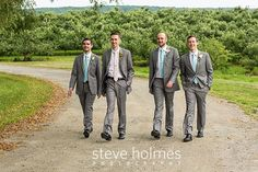 Groom walks with his groomsmen on a dirt road through an orchard. Photo by Steve Holmes Photography