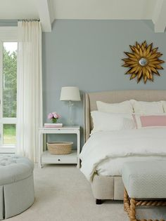 Blue bedroom features a gold sunburst mirror over a wingback bed, Restoration Hardware Warner Fabric Bed, dressed in white bedding and a pink border pillow alongside a blue herringbone bench placed at the foot of the bed.