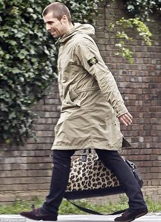 Liam Gallagher rocks cheetah print bag while out with Debbie Gwyther Animal magic: Liam dressed in his usual look for the day as he wore a Stone Island parka and a pair of black trousers Stone Island Hooligan, Stone Island Parka, Liam Oasis, Stone Island Clothing, Ropa On Line, Oasis Band, Fishtail Parka, Italian Outfits, Liam Gallagher