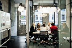 A group of people is sitting at a table during a business meeting in a bright, modern office. The team is talking business while pie charts can be seen hanging on the wall. Big bright windows are seen in the background. Service Public, Le Management, Improve Your Credit Score, Business Meeting, Business Coaching, Strategic Planning, That Way, Content Marketing, Digital Marketing
