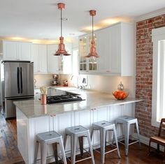 Love the copper accents (mixed with stainless steel) and exposed brick wall in this crisp white kitchen