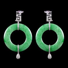 Jade Circle Earrings accompanied by Diamonds and two Rubies. Set in 14 karat White Gold.